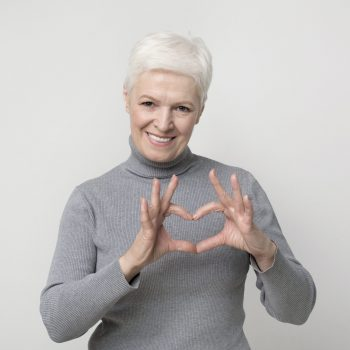 Beautiful aged woman showing heart gesture and smiling on camera