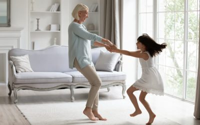 Happy middle-aged grandmother play dancing and swirling in living room with cute little granddaughter, energetic senior granny have fun engaged in childish funny activity with small preschooler child