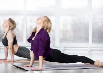 Fitness, stretching practice, group of two attractive smiling fit mature women in sportswear working out in sports club, doing urdhva mukha shvanasana (upward facing dog pose) in class, full length